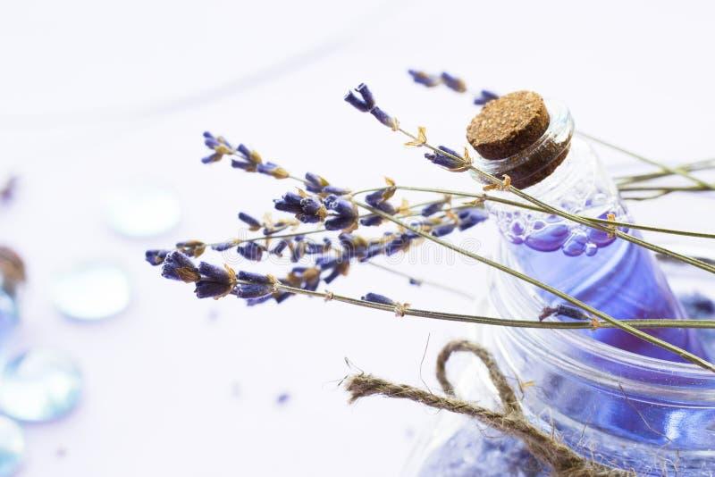 Kuuroord en wellness die met lavendel het plaatsen bloeien, overzees zout, olie in een fles, aromakaars op houten witte achtergro royalty-vrije stock foto