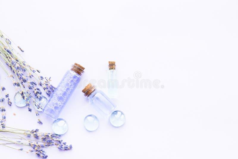 Kuuroord en wellness die met lavendel het plaatsen bloeien, overzees zout, olie in een fles, aromakaars op houten witte achtergro stock foto's