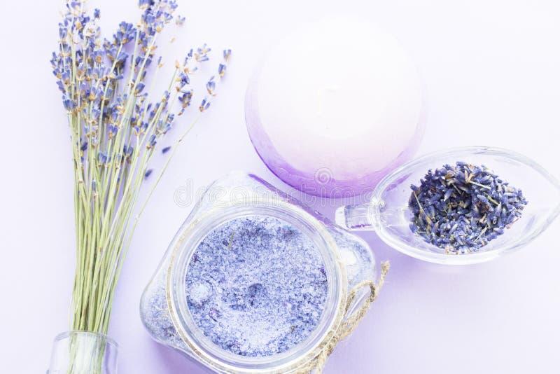 Kuuroord en wellness die met lavendel het plaatsen bloeien, overzees zout, olie in een fles, aromakaars op houten witte achtergro royalty-vrije stock afbeeldingen