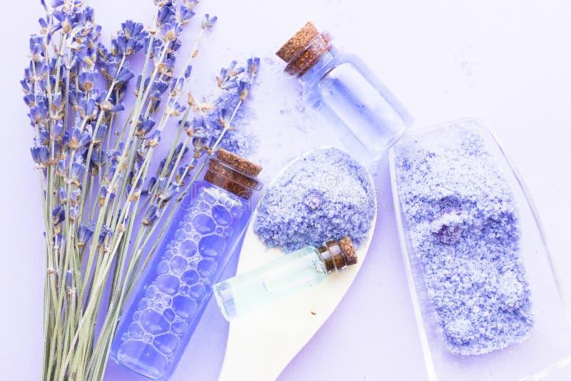 Kuuroord en wellness die met lavendel het plaatsen bloeien, overzees zout, olie in een fles, aromakaars op houten witte achtergro stock afbeelding