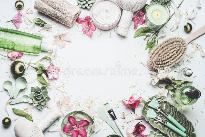 Kuuroord en wellnessachtergrond met bloemen, huidcosmetischee producten en anderen lichaamsverzorging en massagetoebehoren op wit stock foto's