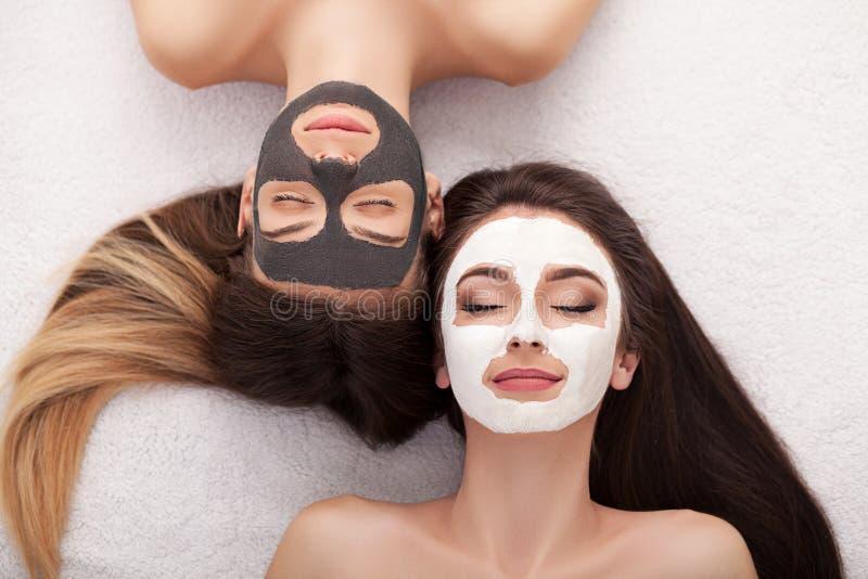 Kuuroord Vrouw met gezichtsmasker en komkommerplakken in haar handen royalty-vrije stock afbeeldingen