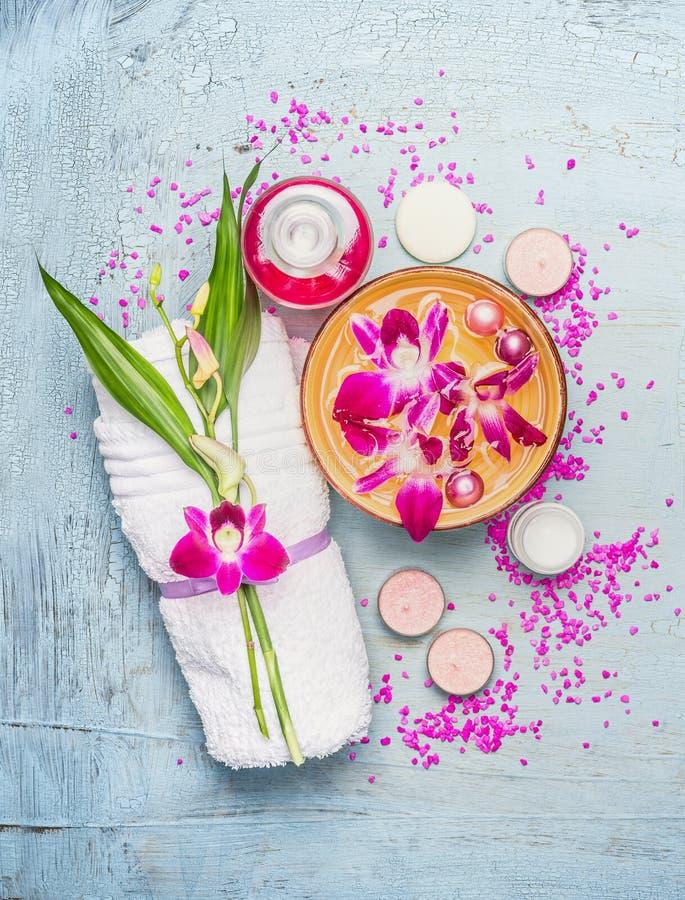 Kuuroord of wellness die met handdoek, bamboebladeren, kom met roze orchideebloemen en water, room, kaarsen en overzees zout plaa stock fotografie