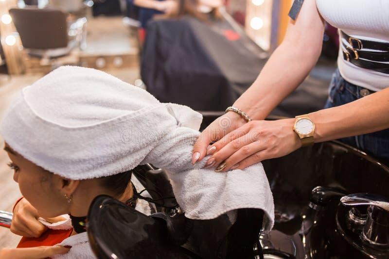 Kuuroordbehandelingen, schoonheidsspecialist, kapper De mooie vrouwelijke cliënt op de stoel na het wassen van haar verpakte haar stock foto's
