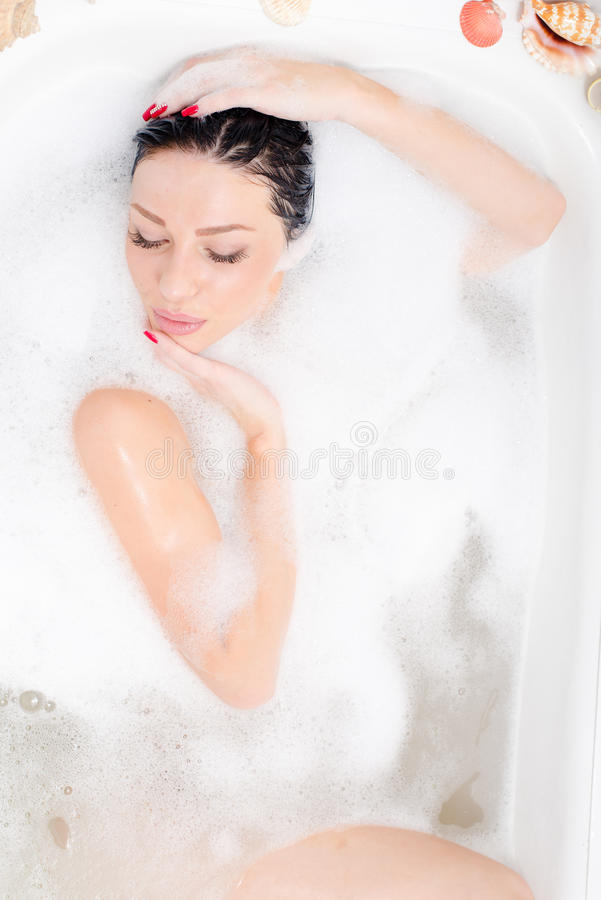 Kuuroordpret: aantrekkelijke mooie seksuele jonge gelukkige vrouw die in het bad met schuimportret liggen stock afbeeldingen