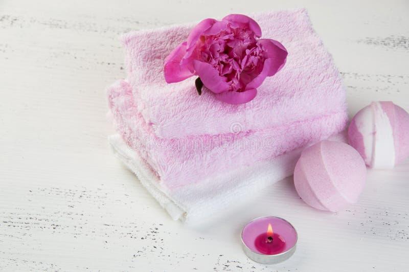 KUUROORDsamenstelling met badbommen en roze pioen stock afbeeldingen