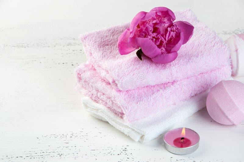 KUUROORDsamenstelling met badbommen en roze pioen stock foto