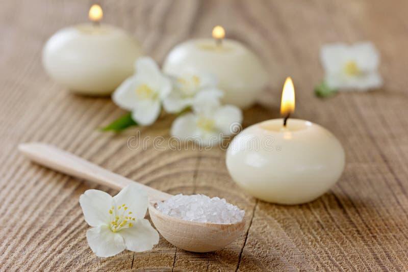 Kuuroordsamenstelling met overzees zout bad in houten lepel, jasmijnbloemen stock afbeelding
