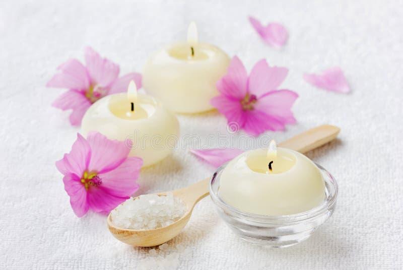 Kuuroordsamenstelling met overzees zout bad in houten lepel, roze bloemen en brandende kaarsen stock afbeeldingen