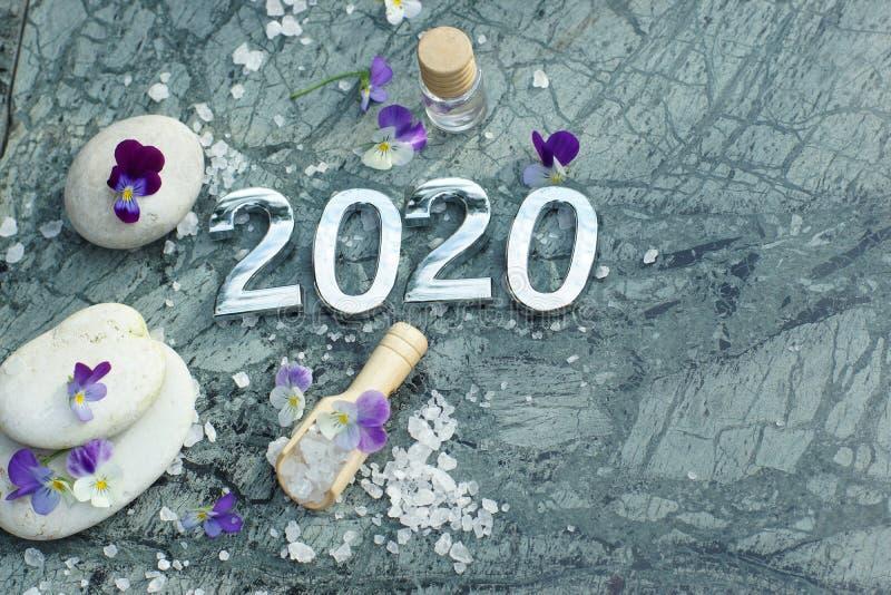 Kuuroordsamenstelling 2020 met purper bloemen, kaarsen, stenen en overzees badzout stock fotografie