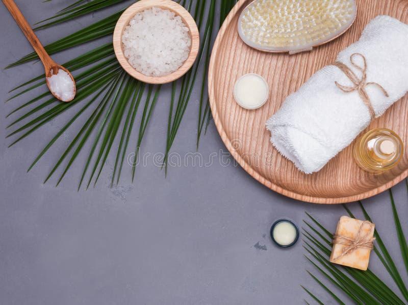 Kuuroordstilleven met droge spoed, witte handdoek en tropische bladeren op de grijze achtergrond stock afbeeldingen