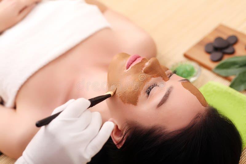 Kuuroordtherapie voor jonge vrouw die gezichtsmasker hebben bij schoonheidssalon - binnen royalty-vrije stock foto