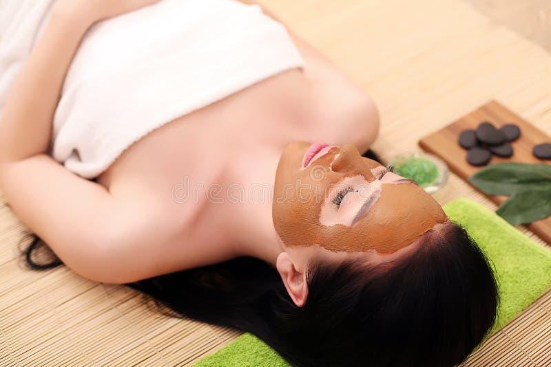 Kuuroordtherapie voor jonge vrouw die gezichtsmasker hebben bij schoonheidssalon - binnen royalty-vrije stock afbeelding