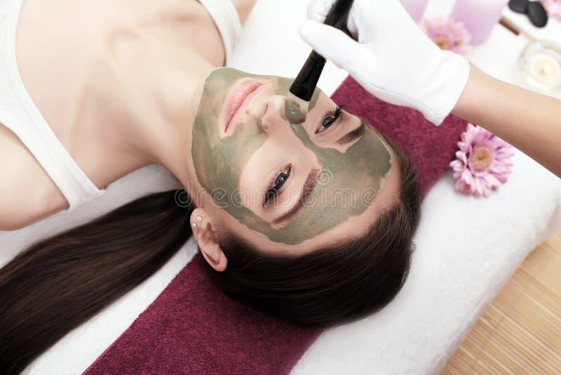 Kuuroordtherapie voor jonge vrouw die gezichtsmasker ontvangen bij schoonheidssalo royalty-vrije stock afbeelding