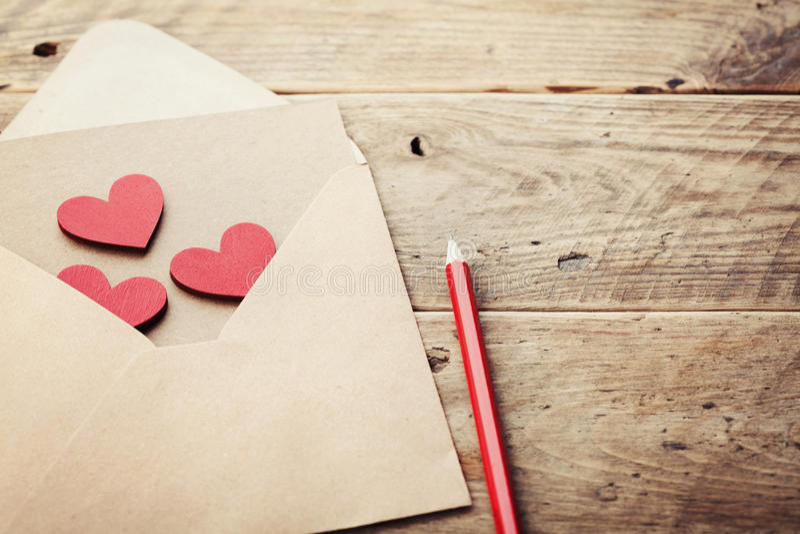 Kuvert eller bokstav och röda hjärtor på den lantliga tabellen för förälskelsemeddelande på valentindag i retro toning arkivfoton