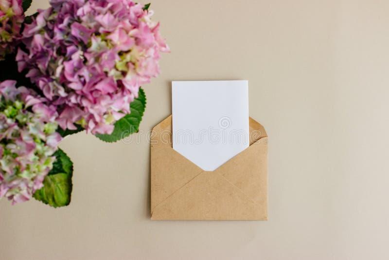 Kuvert för Kraft papper med det vita kortet på ljus bakgrund royaltyfri fotografi