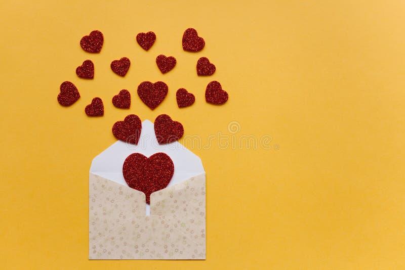 Kuvert med symboler i form av röda hjärtor på en gul bakgrund Beröm royaltyfria bilder