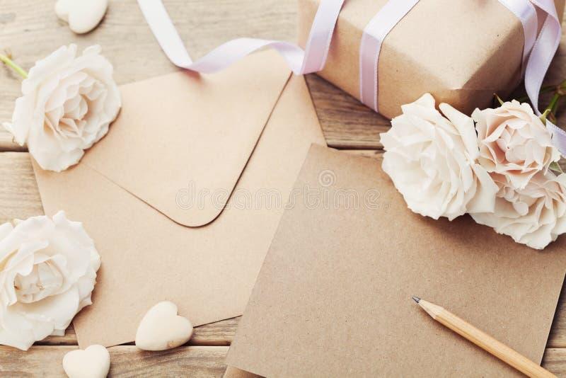 Kuvertet eller bokstaven, gåvan, det pappers- kortet och tappning steg blommor på den lantliga trätabellen för att hälsa på moder fotografering för bildbyråer