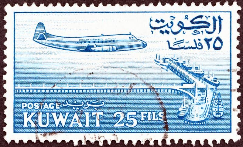 KUWAIT - CIRCA 1961: Un sello impreso en Kuwait muestra el avión y el oleoducto hacia la plataforma petrolera, alrededor de 1961 fotos de archivo