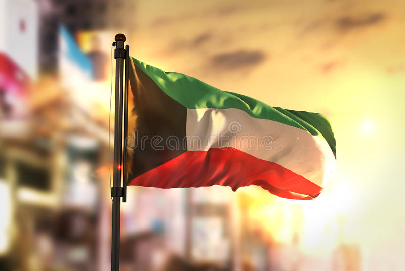 Kuwait Flag Against City Blurred Background At Sunrise Backlight. Sky stock photo