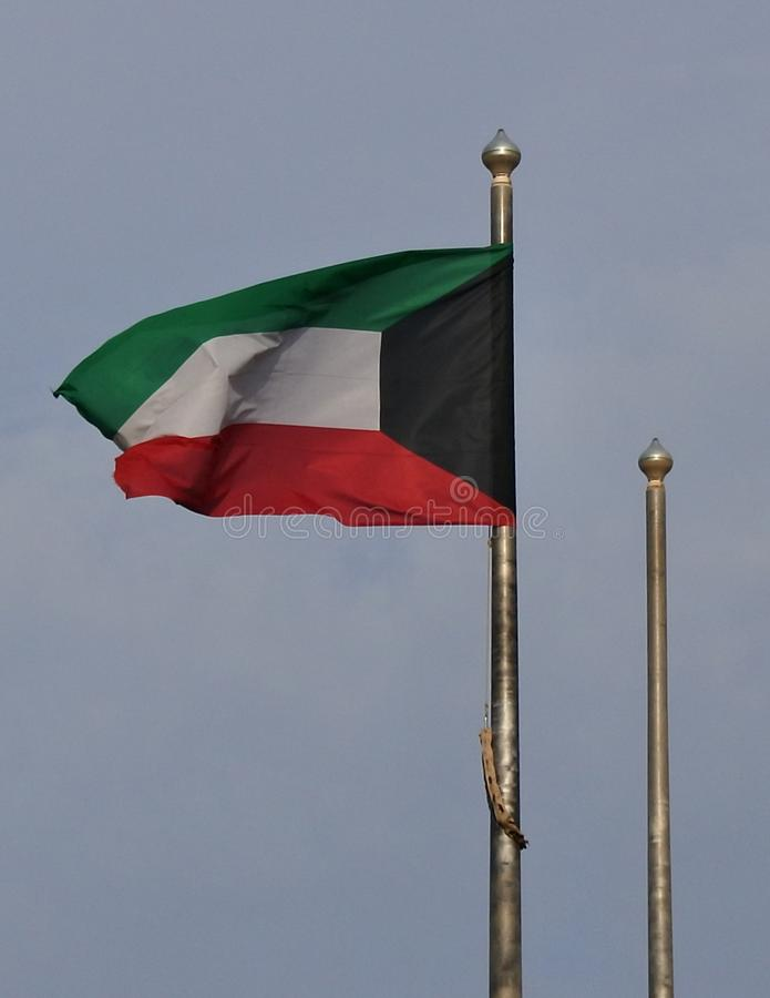 Kuwait Flag Rippling in Breeze. Kuwait`s red, green, white and black flag rippling in the breeze over Kuwait City royalty free stock photos