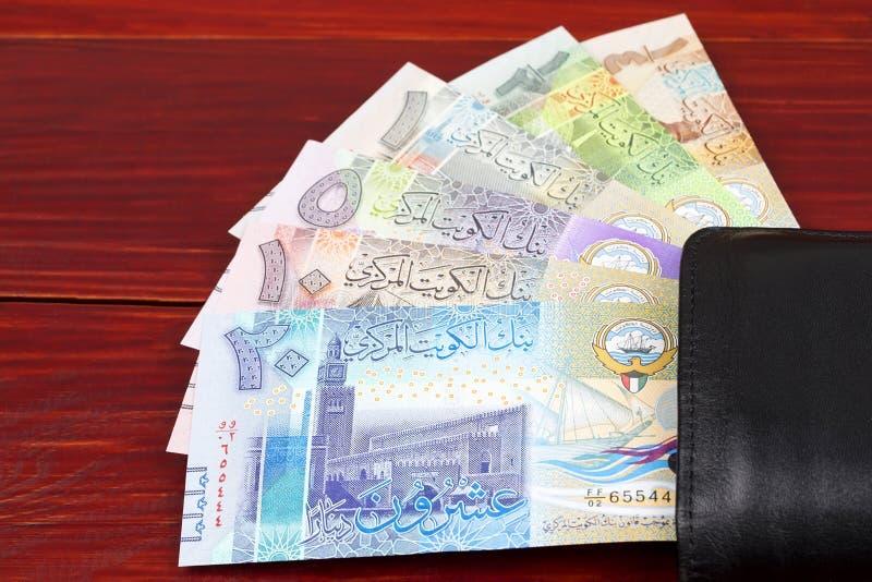 Kuwaitisk dinar i den svarta plånboken royaltyfri fotografi
