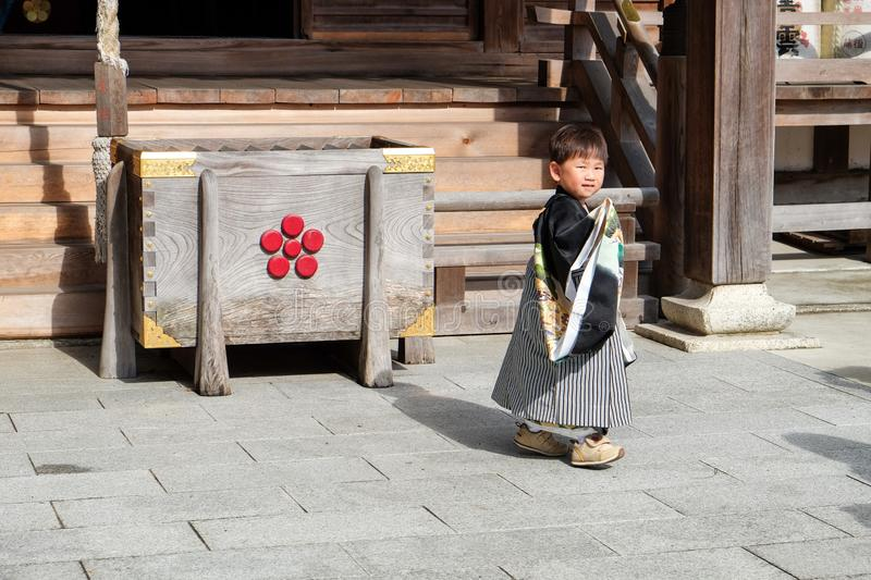Traditional dressed little Japanese boy at wooden temple royalty free stock photography