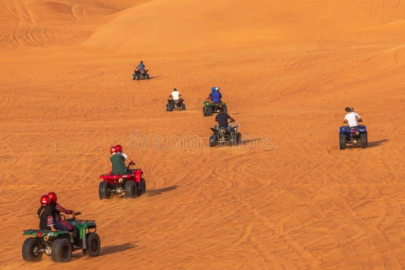Kvadraten som cyklar det Dubai affärsföretaget, turnerar —turister som har gyckel på kvadratcykelridning i dyn av Dubai royaltyfri bild