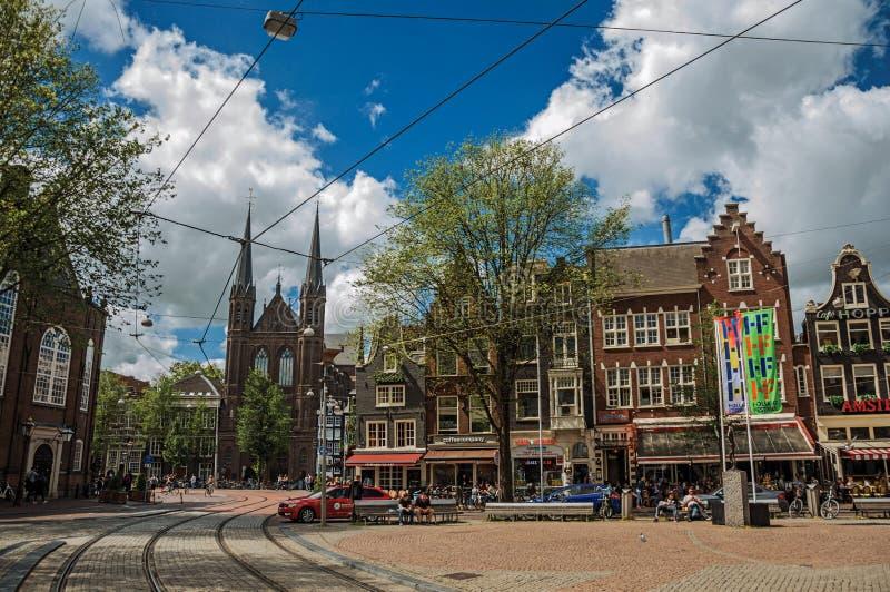 Kvadrera med kyrkliga och typiska byggnader för folk, i Amsterdam arkivfoto