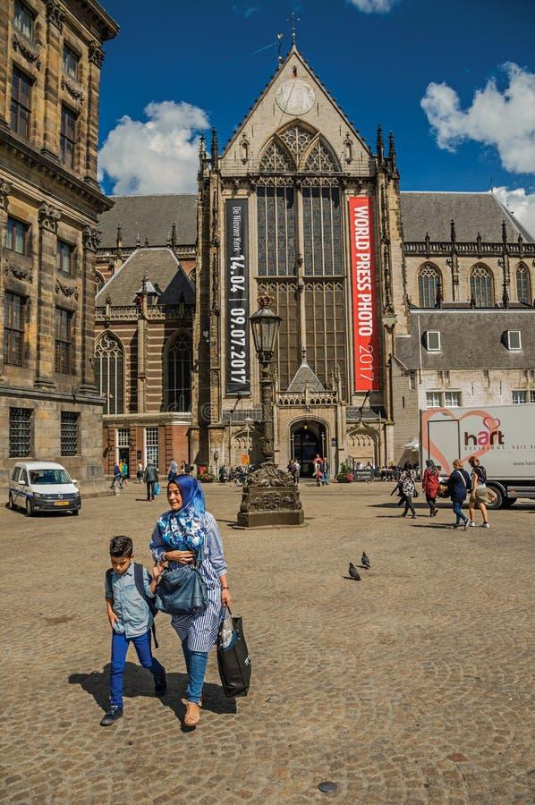 Kvadrerar den bärande hijabsjaletten och barnet för kvinna som går i Amsterdam arkivfoton