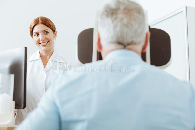 Kvalificerad ögonspecialist som framme sitter av patient arkivbild