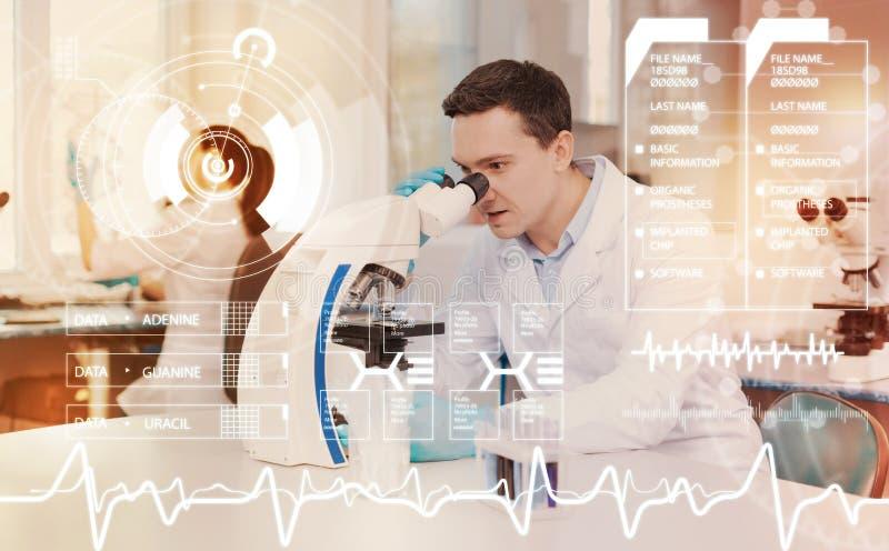 Kvalificerad medicinsk arbetare som ser in i det imponerade mikroskopet och känslan arkivfoto