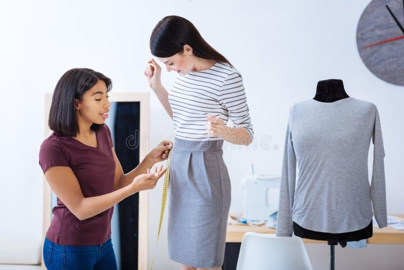 Kvalificerad skräddare som konsulterar hennes klient om typer av klänningar arkivfoton