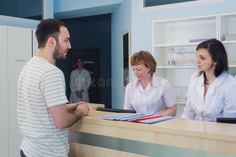 Kvalificerade le doktorer som arbetar med klienten på mottagandeskrivbordet i sjukhus arkivfoto