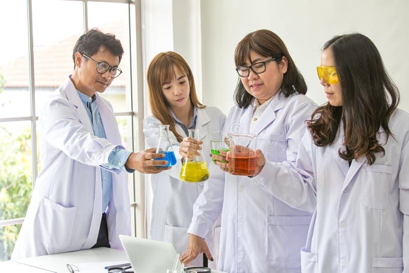 Kvalitet för provning för vetenskapsprovkemist vetenskaplig Gruppforskare som arbetar på laboratoriumet En man och kvinna tre på  royaltyfria foton