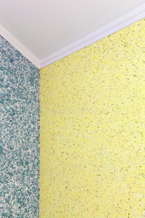Kvalitets- övergång från blått till den gula vätsketapeten i hörnet av rummet royaltyfria bilder