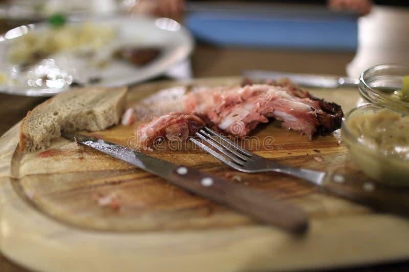 Kvarlevor av stekte grisköttstöd royaltyfri foto