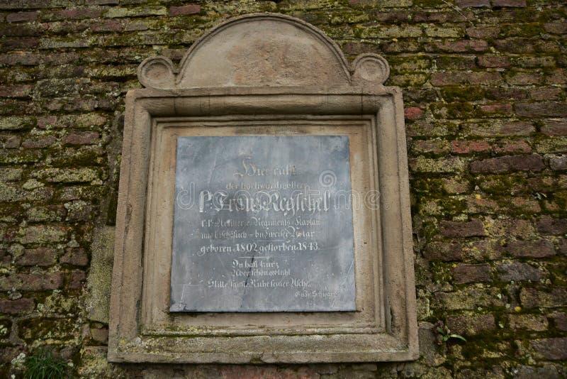 Kvarlevorna av den barocka befästningen i vars vägg det finns flera gravstenar från den gamla militära kyrkogården arkivfoto