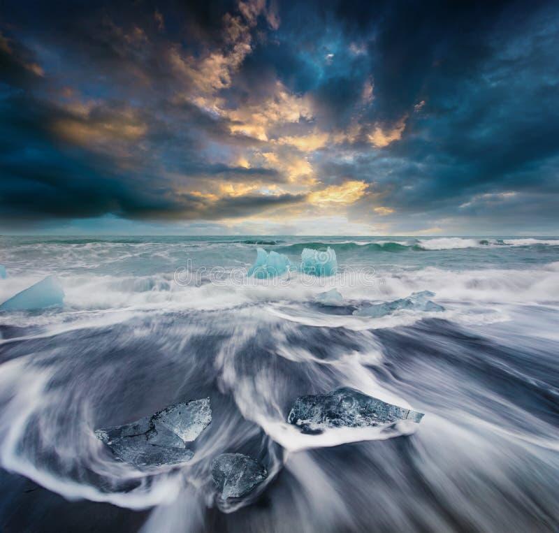 Kvarter av is som tvättas av vågorna på Jokulsarlon, sätter på land royaltyfria bilder