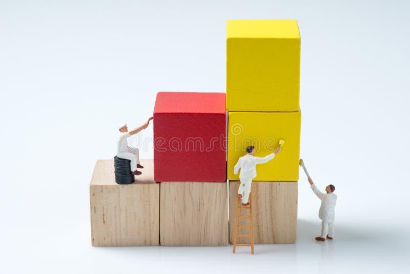 Kvarter för byggnad för kub för miniatyrfolkarbetarmålning wood arkivfoton