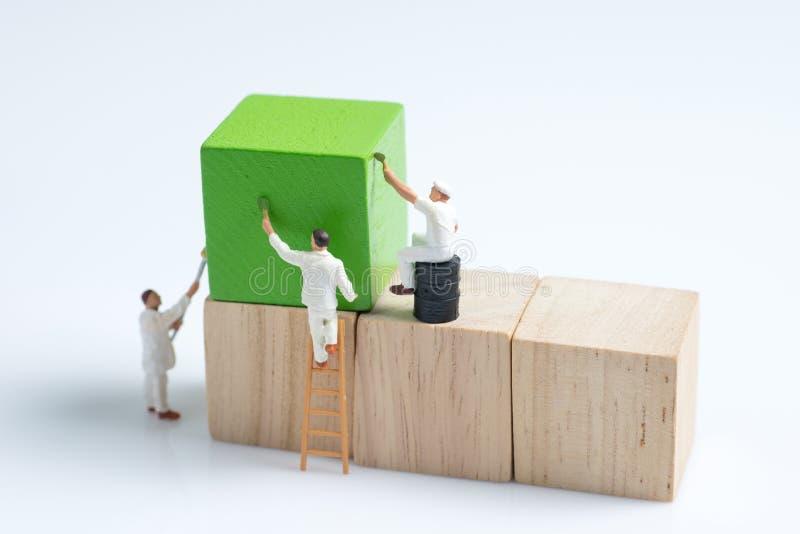 Kvarter för byggnad för kub för miniatyrfolkarbetarmålning wood royaltyfri fotografi