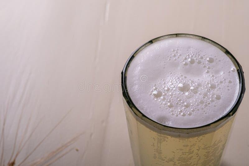 Kvas schiumoso della bevanda fredda fresca della bevanda in vetro sfaccettato su fondo di legno bianco vicino con l'orecchio di g fotografia stock libera da diritti