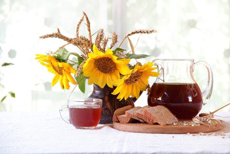 Kvass (kvas) in a transparent jug, bread and a bouquet of sunflo stock photo