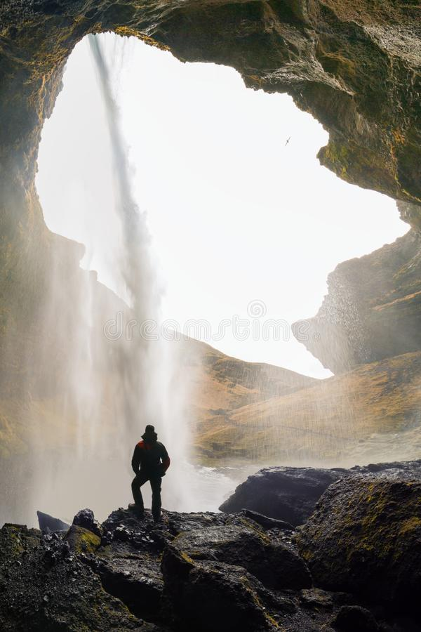 Kvernufoss waterfall at Skogafoss in the gorge of the mountains. Tourist Attractions Iceland A man in a red jacket stands and cave stock photography