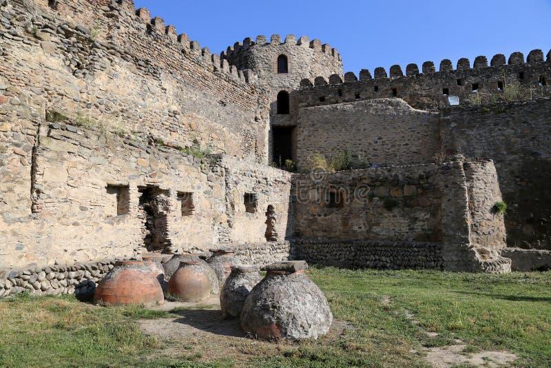 Kvevri antigo - embarcações da argila para fazer o vinho, enterradas na terra sob a parede da fortaleza perto da catedral de Svet imagens de stock royalty free
