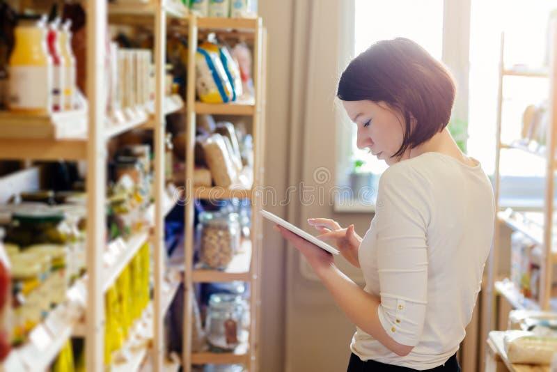Kvinnaägare av lagret med sund mat som beställer produkter med en minnestavla royaltyfri foto