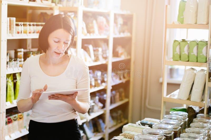 Kvinnaägare av lagret med sund mat som beställer produkter med en minnestavla arkivfoton