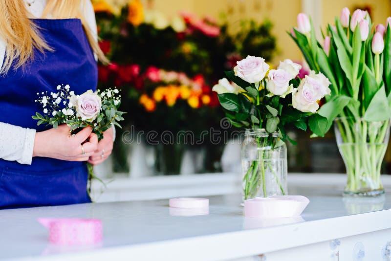 Kvinnaägaren av blomsterhandlaren shoppar förbereda buketten av rosa rosor royaltyfri fotografi