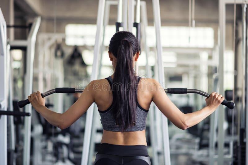 kvinnaövning, genom att pumpa tillbaka i idrottshall arkivfoton