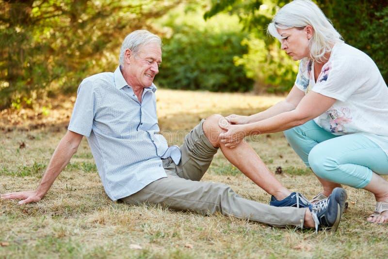 Kvinnaövningsförsta hjälpen på knäet av en gamal man arkivfoton